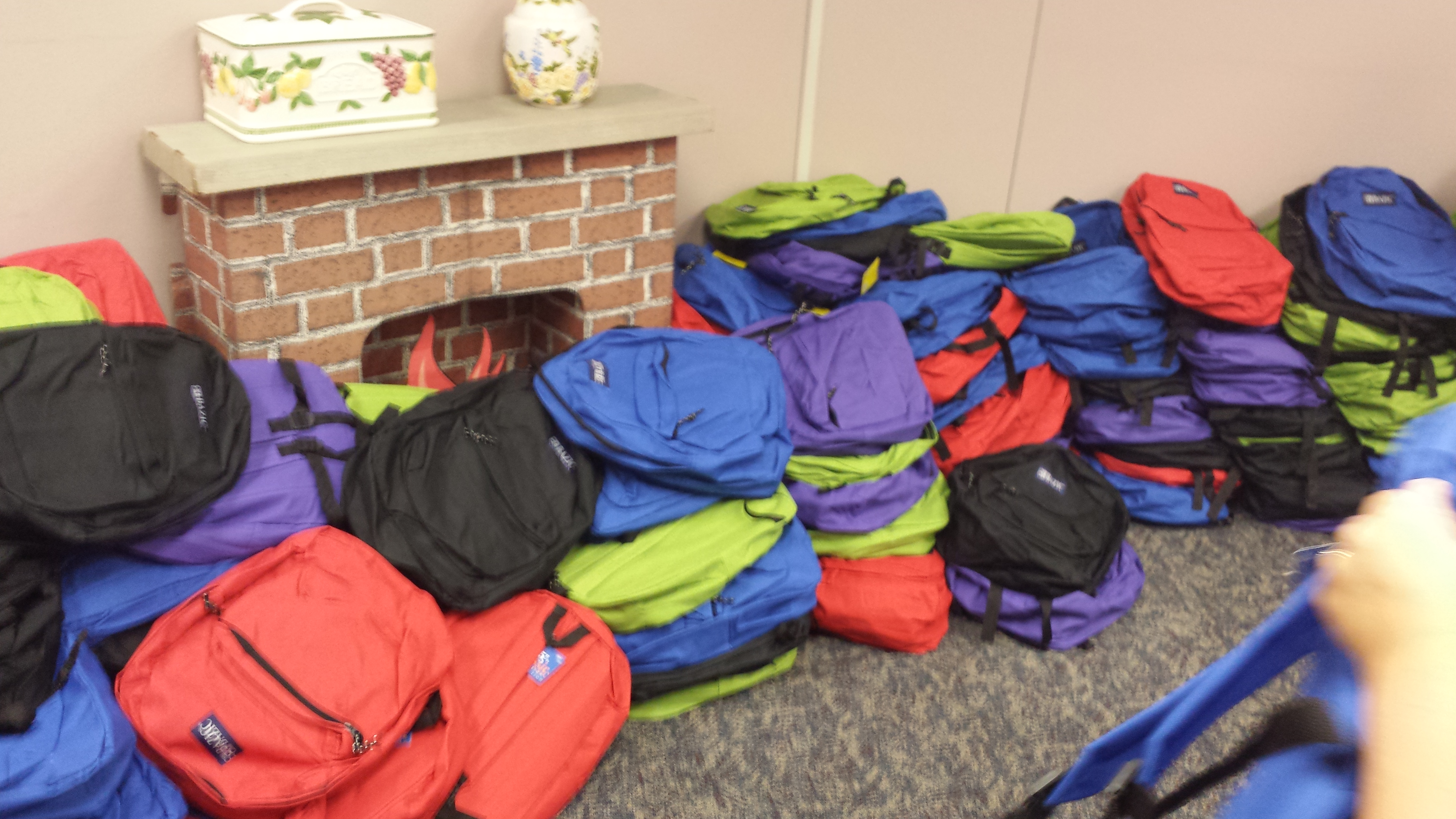 Josee volunteers to fill back packs for children in need lined up